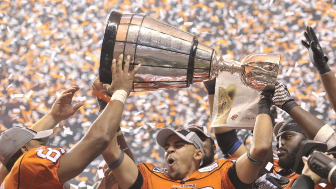 B.C. Lions Andrew Harris hoists the Grey Cup trophy after defeating the Winnipeg Blue Bombers 34-23 in the 99th CFL Grey Cup football game on Sunday, Nov. 27, 2011, in Vancouver, British Columbia. (AP Photo/The Canadian Press, Nathan Denette)