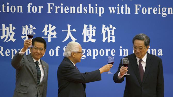 Singapore's Ambassador to China Stanley Loh, Singapore's President Tony Tan Keng Yam and Yu Zhengsheng, chairman of the National Committee of the Chinese People's Political Consultative Conference (CPPCC) toast in Beijing