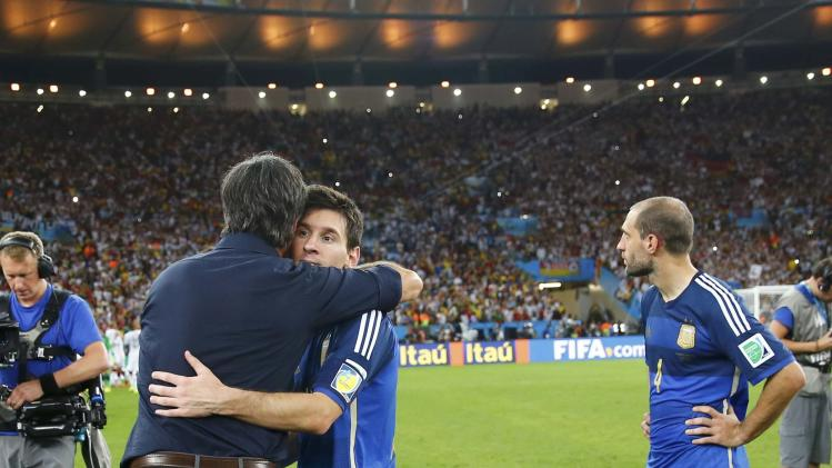 Germany's coach Joachim Loew hugs Argentina's Lionel Messi after the 2014 World Cup final between Germany and Argentina at the Maracana stadium