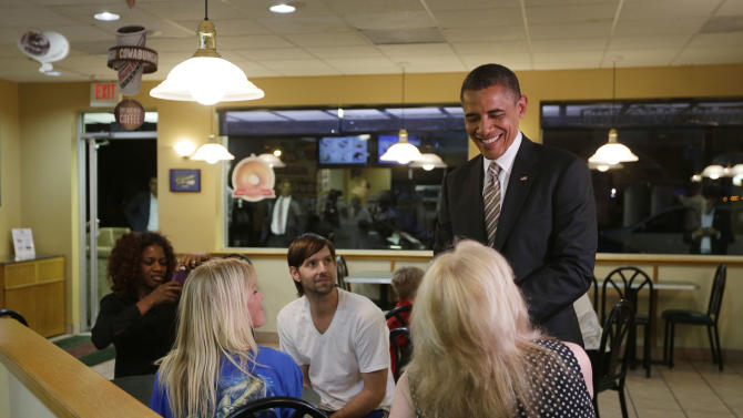 President Barack Obama greets local patron during an unannounced visit to Krispy Kreme Doughnuts shop, Thursday, Oct. 25, 2012, in Tampa, Fla. Obama, who traveled to Florida for a campaign event nearby, surprised local patrons when he drove up in the morning. (AP Photo/Pablo Martinez Monsivais)