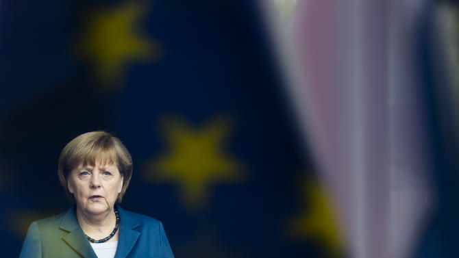 German Chancellor Angela Merkel stand behind a window with a reflection of the European flag as she waits for the arrival of King Willem-Alexander of the Netherlands and Queen Maxima of the Netherlands, unseen, for a meeting at the chancellery in Berlin, Monday, June 3, 2013. (AP Photo/Markus Schreiber)