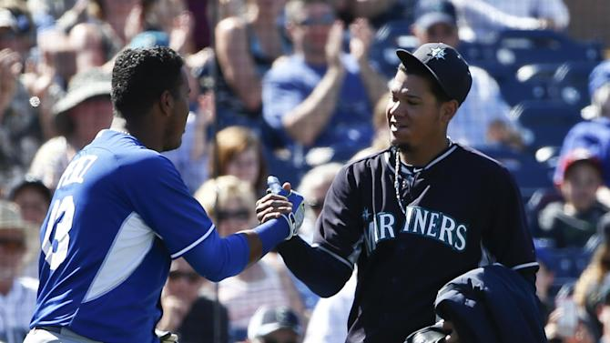 Seattle Mariners starting pitcher Felix Hernandez and Kansas City Royals catcher Salvador Perez greet each other as Hernandez leaves the field after pitching six innings against the Royals and allowed only one run and two hits of a spring training baseball game Thursday, March 26, 2015, in Peoria, Ariz.  (AP Photo/Lenny Ignelzi)