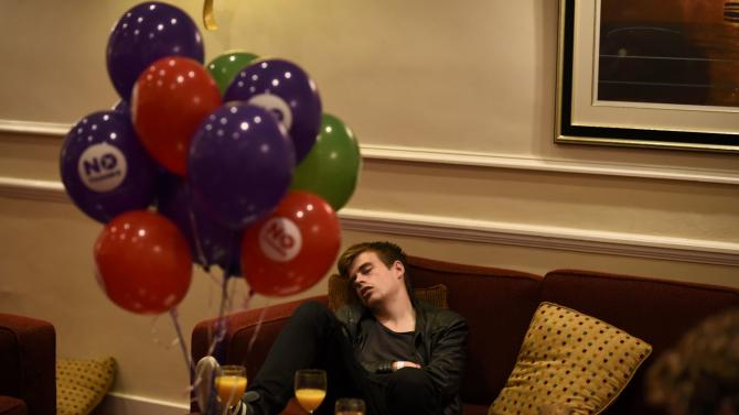 "A supporter from the ""No"" Campaign sleeps as he waits for the announcement of results, at the Better Together Campaign headquarters in Glasgow, Scotland"