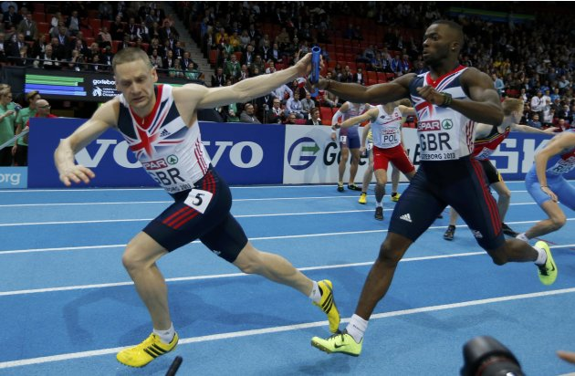 Team Britain's Strachan relays Levine during the 4x400m Relay Men Final at the European Athletics Indoor Championships in Gothenburg