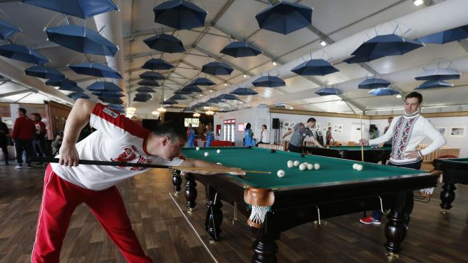 Speed skating coach Andrey Saveliev of Russia uses the pool table in the Coastal Athlete's Village at the Sochi 2014 Winter Olympics