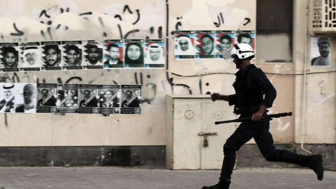 A Bahraini riot policeman chases anti-government protesters, unseen, during clashes in Sitra, Bahrain, Monday, Sept. 3, 2012. Pictures of people killed in the unrest, jailed political leaders and images of British Prime Minister David Cameron and U.S. President Barack Obama depicted as criminals for their close relations with the monarchy are plastered on the wall. Verdicts are expected Tuesday for numerous jailed leaders, medical workers and activists. (AP Photo/Hasan Jamali)