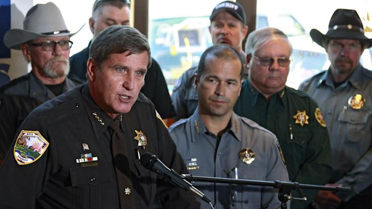 Weld County, Colo., Sheriff John Cooke, left, with El Paso County Sheriff Terry Maketa, center right, and other sheriffs standing behind him, speaks during a news conference at which he announced that 54 Colorado sheriffs are filing a federal civil lawsuit against two gun control bills passed by the Colorado Legislature, in Denver, Friday, May 17 2013. Among other claims, the group of sheriffs and others joining the suit argue that the laws violate the 2nd and 14th Amendments of the U.S. Constitution. (AP Photo/Brennan Linsley)