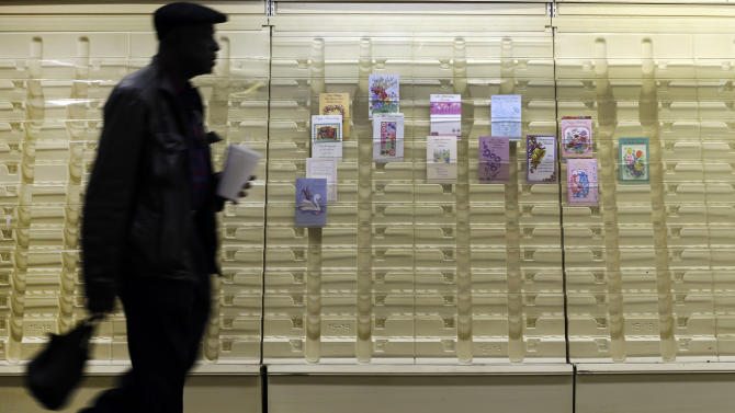 In this April 27, 2013 photo, a man walks past a greeting cards display case in a market in Baltimore.The private Conference Board reports on consumer confidence for April on Tuesday, April 30, 2013 (AP Photo/Patrick Semansky)