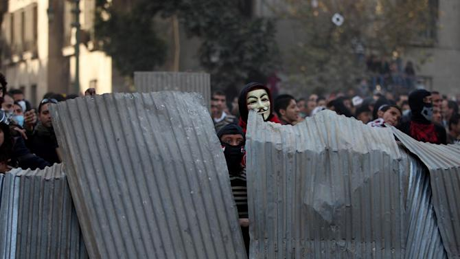 Egyptian protesters take cover as they clash with riot police, not seen, near Tahrir Square, Cairo, Egypt, Friday, Jan. 25, 2013. Youth activists and opposition groups have called for large rallies to mark the second anniversary of Egypt's Jan. 25, 2011 uprising that toppled long-time authoritarian leader President Hosni Mubarak. (AP Photo/Khalil Hamra)