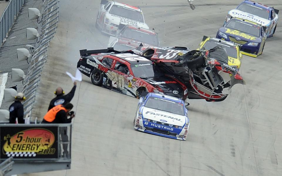 Driver Clint Bowyer (33) collides with Joey Logano (20) during the NASCAR Nationwide series 5-hour ENERGY 200 auto race, Saturday, May 14, 2011, at Dover International Speedway in Dover, Del. Driver Carl Edwards (60) is at front. (AP Photo/Nick Wass)