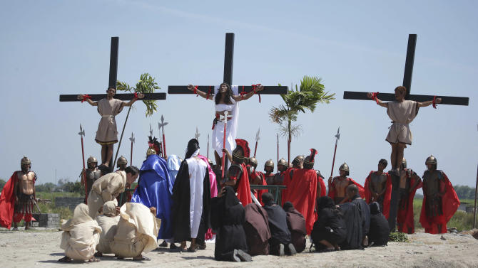 Filipino penitent Ruben Enaje, center, who has portrayed as Jesus Christ for 27 times, is nailed on the cross as he leads others in a reenactment of the crucifixion of Jesus Christ during Good Friday rituals on March 29, 2013 at Cutud, Pampanga province, northern Philippines. Several Filipino devotees had themselves nailed to crosses Friday to remember Jesus Christ's suffering and death, an annual rite rejected by church leaders in this predominantly Roman Catholic country. (AP Photo/Aaron Favila)