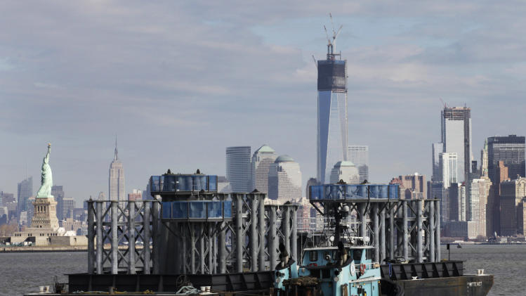 A barge loaded with sections of spire for One World Trade Center, center, is guided by tugboat across New York Harbor, Tuesday, Dec. 11, 2012 in New York. The Statue of Liberty is at left, and the Empire State Building is second left. (AP Photo/Mark Lennihan)