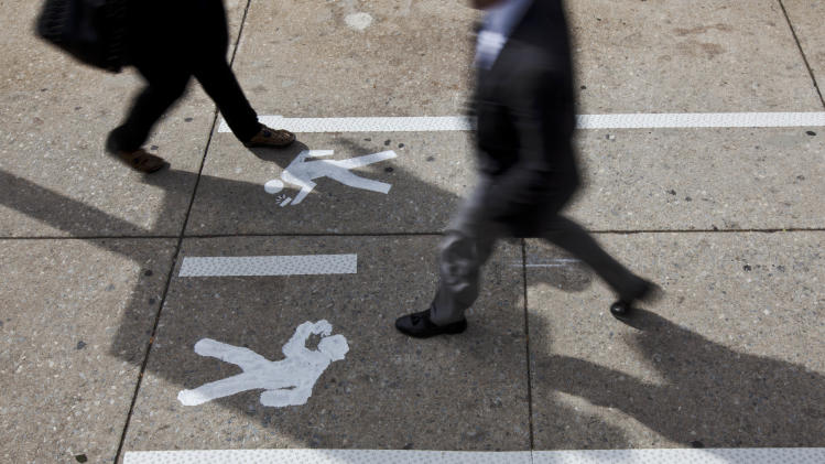 "Pedestrians walk through an ""e-lane"" Monday, April 2, 2012, in Philadelphia. Philadelphia Mayor Michael Nutter used April Fool's Day to have a little fun with what he says is a real problem: distracted walking. City officials painted lines and oblivious stick-figure pictures on one stretch of John F. Kennedy Boulevard near City Hall as a jab at pedestrians who keep their eyes on their cellphone screens and not their surroundings. (AP Photo/Matt Rourke)"