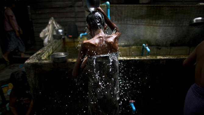 In this Aug. 27, 2012 photo, an HIV-infected patient scoops water over her head to cool down on a hot summer day at an HIV/AIDS center on the outskirts of Yangon, Myanmar. Following a half century of military rule, care for HIV/AIDS patients in Myanmar lags behind other countries. Half of the estimated 240,000 people living with the disease are going without treatment and 18,000 are dying from it every year. (AP Photo/Alexander F. Yuan)