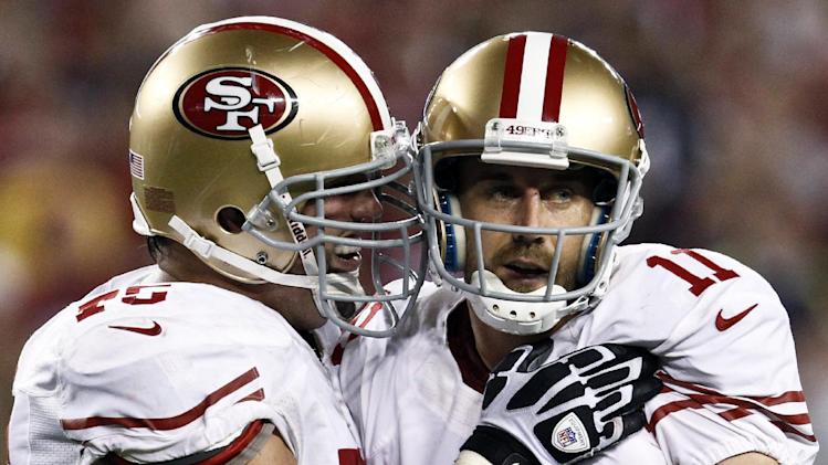 San Francisco 49ers' Alex Smith (11) celebrates his second touchdown pass of the game against the Arizona Cardinals with Alex Boone, left, during the first half of an NFL football game, Monday, Oct. 29, 2012, in Glendale, Ariz. (AP Photo/Ross D. Franklin)