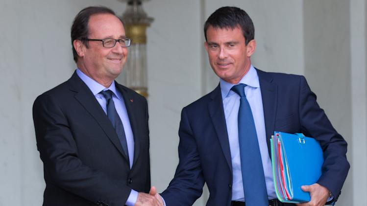 French President Hollande and Prime Minister Valls leave the Elysee Palace in Paris, following the weekly cabinet meeting