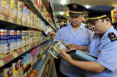 Local industry and commerce administrative bureau personnel check Sanlu formula milk products at a supermarket in Zaozhuang
