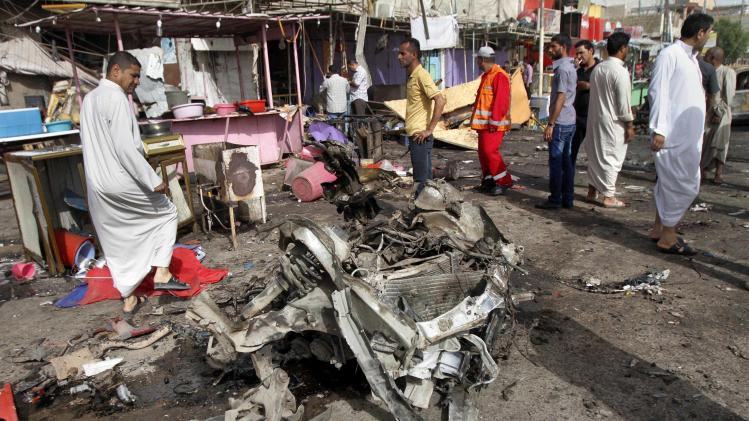 Civilians gather at the site of a car bomb attack in front of a crowded popular restaurant in Basra, 340 miles (550 kilometers) southeast of Baghdad, Iraq, Monday, May 20, 2013. Two car bombings in the southern city of Basra, killing and wounding dozens of people, police said. Iraq has seen a spike of attacks, including bombings hitting both Sunni and Shiite civilian targets over the last week. (AP Photo/ Nabil al-Jurani)