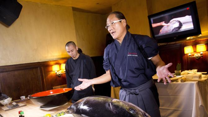 """IMAGE DISTRIBUTED FOR KIKKOMAN USA - In this photo released on Monday Dec. 10, 2012, Chef Morimoto performs a live demonstration for Kikkoman's """"Make Haste Slowly"""" event at Tribeca Cinemas in New York. (Photo by Charles Sykes/Invision for Kikkoman USA/AP Images)"""