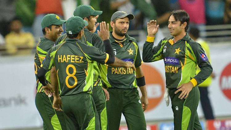 Pakistan bowler Saeed Ajmal, right, celebrates with Shahid Afridi, second right, and team the wicket of Sri Lanka Kumar Sangakkara (caught by Afridi) during the first T20 cricket match between Pakistan and Sri Lanka, at the DSC Cricket Stadium Dubai, United Arab Emirates, Wednesday, Dec. 11, 2013