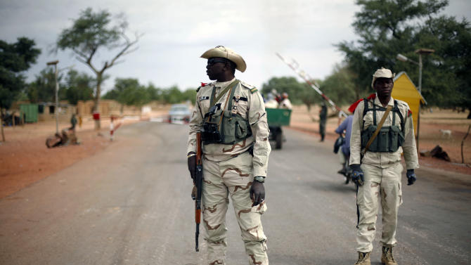 Malian soldiers man a checkpoint on the Gao road outside Sevare, some 620 kilometers (385 miles) north of Mali's capital  Bamako, Sunday, Jan. 27, 2013. French and Malian troops held a strategic bridge and the airport in the northern town of Gao on Sunday as their force also pressed toward Timbuktu, another stronghold of Islamic extremists in northern Mali, officials said. (AP Photo/Jerome Delay)