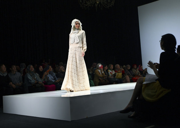 In this Saturday, May 31, 2013 photo, a model showcases a creation by Indonesian designer Irna Mutiara during the Islamic Fashion Fair in Jakarta, Indonesia. The event is part of the Indonesian government's effort to turn the most populous Muslim country into the world's Islamic fashion capital by 2020. (AP Photo/Dita Alangkara)