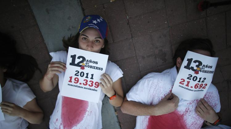 Anti-government protesters hold placards with the numbers of deaths by violence per year during a rally against violence in Caracas