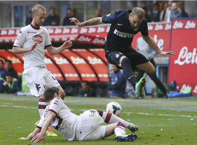 Inter Milan forward Rodrigo Palacio, top right, of Argentina, is tackled by Torino defender Marko Vesovic, bottom, of Montenegro, as Torino midfielder Migjen Basha, of Switzerland, looks them during t