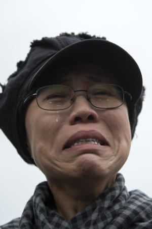FILE - In this June 9, 2013 file photo, Liu Xia, the wife of imprisoned Nobel Peace Prize winner Liu Xiaobo, cries outside Huairou Detention Center where her brother Liu Hui has been jailed in Huairou district, on the outskirts of Beijing, China. The health of Liu Xia has deteriorated under lengthy house arrest and she urgently requires medical treatment, close friends said Friday, Feb. 14, 2014. (AP Photo/Alexander F. Yuan, File)