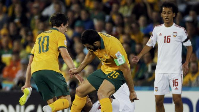 Australia's Robbie Kruse holds his boot while attempting to defend against UAE's Omar Abdulrahman during their Asian Cup semi-final soccer match at the Newcastle Stadium in Newcastle