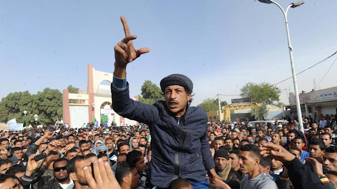 In this photo dated March 14, 2013, protesters gestures during a demonstration by thousands of young unemployed men demanding jobs in the oil industry in Algeria's southern city of Ouargla. Protests by the unemployed in southern Algeria are raising the specter of rising unrest in the country's sensitive oil regions, and are increasingly attracting the attention of al-Qaida. (AP Photo/Nabil Zahani)