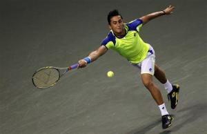 Almagro of Spain returns a shot against Nishikori of Japan during their men's singles quarter final match at the Japan Open tennis championships in Tokyo