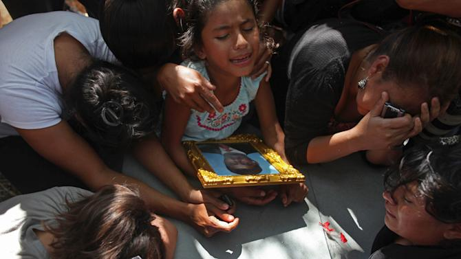 Relatives of inmate Nery Ricardo Gomez hold onto a framed portrait of him as they grieve on his coffin during his burial service at the cemetery in Comayagua, Honduras, Saturday Feb. 18, 2012. Gomez perished in the fire that swept through the Comayagua prison north of Tegucigalpa late Tuesday. A Honduran doctor said Saturday morning that another man has died from injuries sustained in the deadly prison fire, bringing the death toll to 358. (AP Photo/Esteban Felix)