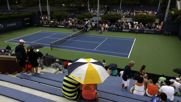 Spectators wait out a rain delay on Court 7 during the 2013 U.S. Open tennis tournament, Wednesday, Aug. 28, 2013, in New York. (AP Photo/Mike Groll)