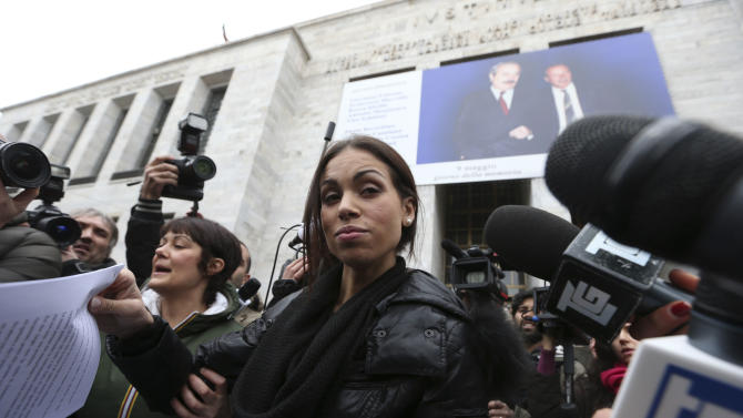 FILE - In this , Thursday, April 4, 2013 file photo Karima el-Mahroug, also known as Ruby, a Moroccan woman at the center of ex-Premier Silvio Berlusconi's sex-for-hire trial, hands out the statement she read to reporters outside Milan's court house , Thursday, April 4, 2013. Former Premier Silvio Berlusconi faces a verdict in his sensational sex-for-hire trial, charges that could bring an end to his two-decade political career. Berlusconi is charged with paying an under-age Moroccan teen for sex and then trying to cover it up with phone calls to Milan police officials when she was picked up for alleged theft. Berlusconi and the woman deny having had sex with each other. A court is expected to deliver a verdict Monday, June 24, 2013. (AP Photo/Luca Bruno, file )