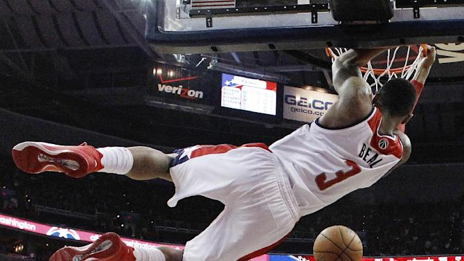 Washington Wizards guard Bradley Beal hangs from the basket after dunking the ball during the second half of Game 3 of an Eastern Conference semifinal NBA basketball playoff game against the Indiana Pacers in Washington, Friday, May 9, 2014. The Pacers won 85-63