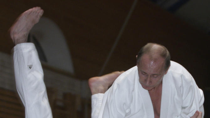 FILE - In this Friday, Dec. 18, 2009 file photo, then Russian Prime Minister Vladimir Putin, top, is seen during judo training at a sports school in St. Petersburg, Russia. Vladimir Putin turns 60-years old on Sunday, Oct. 7, 2012, and has recently sought to demonstrate his youthful vigor by many personal endeavors, but while he has shown creativity in his action-man stunts, the Russian president seems surprisingly vulnerable to the vagaries of oil prices.  (AP Photo/RIA Novosti, Alexei Druzhinin, Government Press Service, file)