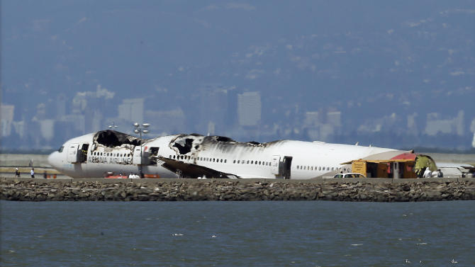 """The wreckage of Asiana Airlines Flight 214 that crashed upon landing Saturday at San Francisco International Airport sits on the tarmac Monday, July 8, 2013 in San Francisco. Investigators said the Boeing 777 was traveling """"significantly below"""" the target speed during its approach and that the crew tried to abort the landing just before it smashed onto the runway on Saturday, July 6. Two of the 307 passengers aboard were killed. (AP Photo/Jeff Chiu)"""