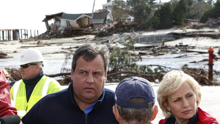 New Jersey Gov. Chris Christie, left, stands with Lt. Gov. Kim Guadagno, right, as they listen to Bay Head Mayor Chris Curtis and D'Arcy Rohan Green, of Bay Head,  near destroyed homes along the Atlantic Ocean Friday, Nov. 2, 2012, in Manoloking, N.J. Christie toured some of the region devastated by Monday's storm surge from Superstorm Sandy. (AP Photo/Mel Evans, pool)