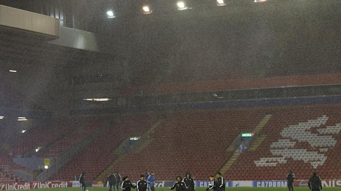 Real Madrid players react as heavy rain falls as they train at Anfield Stadium, in Liverpool, England, Tuesday, Oct. 21, 2014. Real Madrid will play Liverpool in a Champion's League Group B soccer match on Wednesday. (AP Photo/Jon Super)