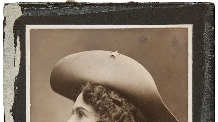 This handout photo, provided by Heritage Auctions, shows Annie Oakley in one of her cabinet photos. Oakley wears the dark wig she wore for The Western Girl was taken in New York between 1902 and 1904. Relatives of Oakley are selling items that once belonged to the legendary sharpshooter including a Stetson hat, guns, letters and photographs. Heritage Auctions will offer up about 100 items related to Oakley on Sunday in Dallas.(AP Photo/Courtesy of Heritage Auctions)