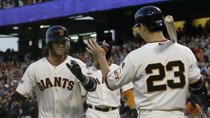 San Francisco Giants' Brandon Crawford, left, is congratulated by Nori Aoki (23) after hitting a two-run home run that scored Hunter Pence, rear, against the Milwaukee Brewers during the fourth inning of a baseball game in San Francisco, Monday, July 27, 2015. (AP Photo/Jeff Chiu)