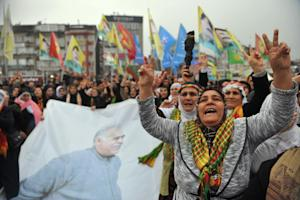 Kurdish demonstrators hold up a banner with a portrait…