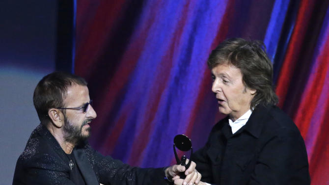 Paul McCartney, right, hands the trophy to Ringo Star at the Rock and Roll Hall of Fame Induction Ceremony Sunday, April 19, 2015, in Cleveland. (AP Photo/Mark Duncan)