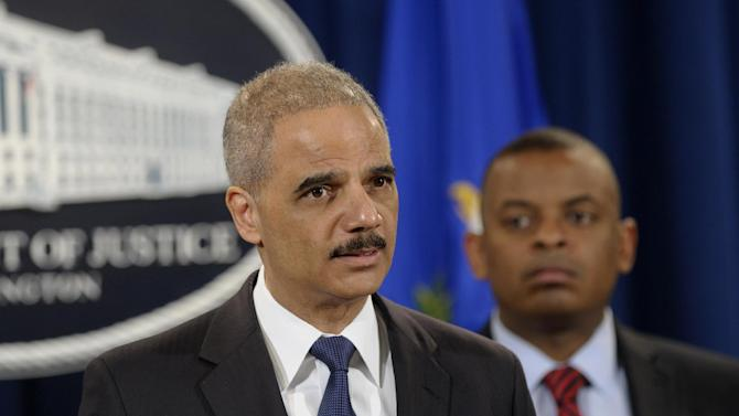 Attorney General Eric Holder, left, accompanied by Transportation Secretary Anthony Foxx, announces a $1.2 billion settlement with Toyota over its disclosure of safety problems, Wednesday, March 19, 2014, during a news conference at the Justice Department in Washington. (AP Photo/Susan Walsh)