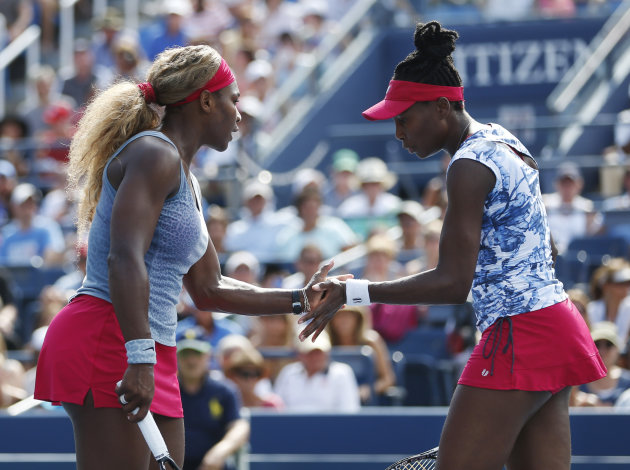 Serena, left, and Venus Williams slap hands between points against Garbine Muguruza and Carla Suarez Navarro, of Spain, during a doubles match at the ...