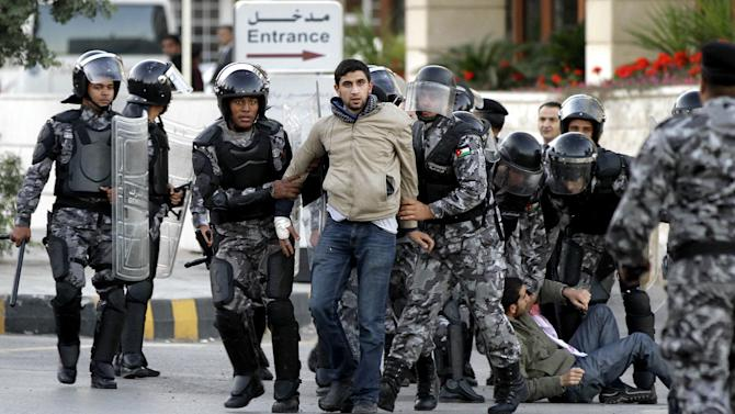 Jordanian policemen detain protesters blocking a main road during a demonstration against a rise in fuel prices in downtown Amman, Jordan, Wednesday, Nov. 14, 2012. Hundreds of Jordanians chanted slogans against the king and threw stones at riot police as they protested in several cities for a second day Wednesday amid rising anger over fuel price hikes. (AP Photo/Raad Adayleh)