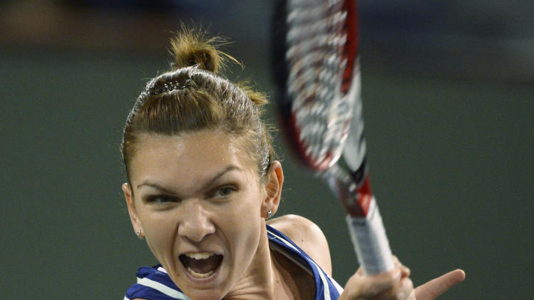 Simona Halep, of Romania, reacts after hitting to Agnieszka Radwanska, of Poland, during their semifinal match at the BNP Paribas Open tennis tournament, Friday, March 14, 2014, in Indian Wells, Calif. (AP Photo/Mark J. Terrill)