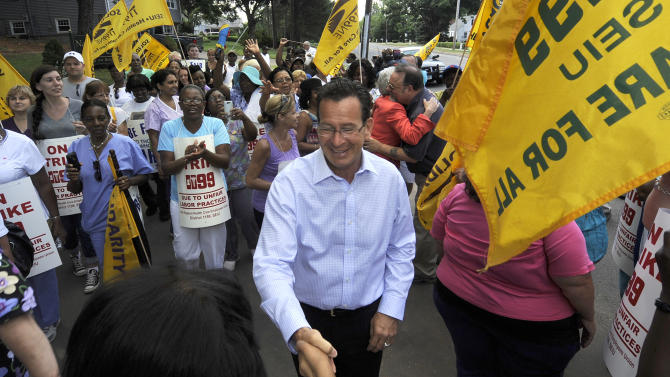 """Connecticut Gov. Dannel P. Malloy meets with striking nursing home workers at Newington Health Care Center in Newington, Conn., Wednesday, July 11, 2012. Workers at five HealthBridge-owned nursing homes around the state went on strike last week after the health care company declined to return to the bargaining table. Malloy said it's clear the company has taken """"unfair actions"""" against employees, citing last week's federal complaint against the company issued by the National Labor Relations Board. (AP Photo/Jessica Hill)"""