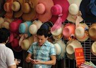 A vendor selling hats does business on a shopping street in Shanghai in July 2012. Chinese inflation hit a two-and-a-half-year low in July, official data showed Thursday, giving the government further policy leeway to boost weakening growth